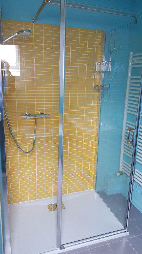 Douche à l'italienne avec grand receveur blanc. Faience intérieure jaune, parois vitrées transparentes, faience extérieure bleu azur et sèche serviette. Réalisé par AG2P, expert en plomberie et systèmes de chauffage