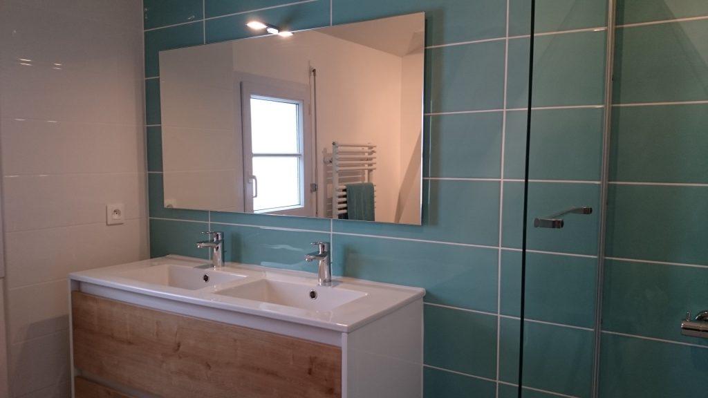 Salle de bain faiencée et installée par AG2P expert en plomberie et chauffage à Nantes. Grand miroir, meuble double vasque blanc et bois, faïence bleu clair